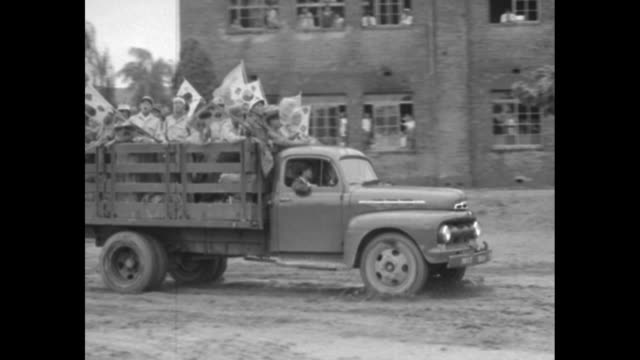 Civilians stand on hillside / truck loaded with soldiers waving Korean flags passes on road / soldiers wave Korean flags as truck pulls up to...