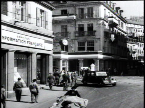 civilians walking along city streets, cars driving on the road beside them / germany - nachkriegszeit stock-videos und b-roll-filmmaterial