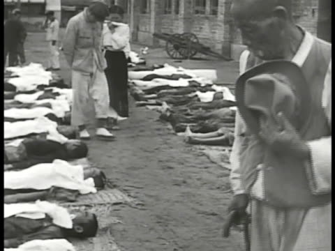 civilians walking between rows of bodies, dead people, unidentified soldiers or civilians, casualties. woman in traditional coat lifting cloth to see... - grief stock videos & royalty-free footage