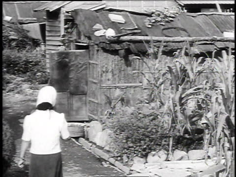 civilians walking outside of a damaged home / civilian entering a damaged home - 1940~1949年点の映像素材/bロール
