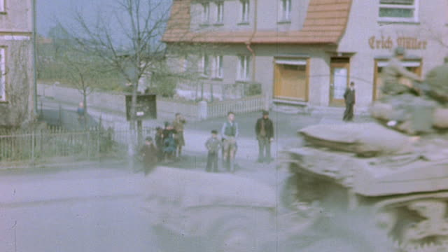 civilians watching us army armored convoy rolling through town past sign reading zur wache / germany - 1945 stock-videos und b-roll-filmmaterial