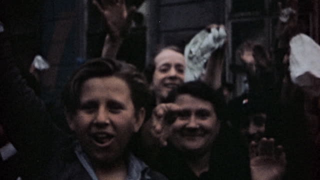 civilians waving and celebrating in streets / pilsen czech republic - ve day stock-videos und b-roll-filmmaterial