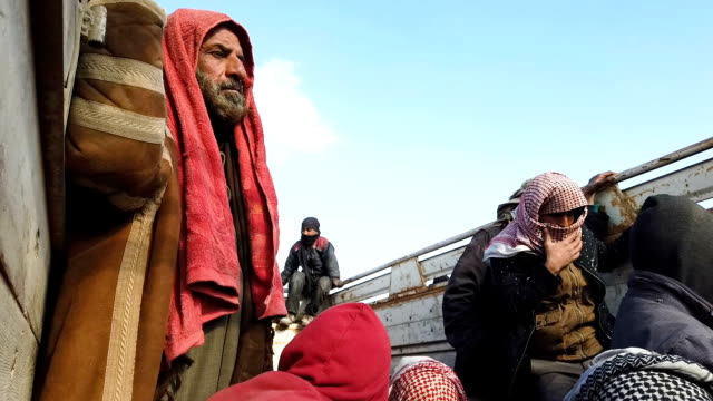 civilians who have fled fighting in bagouz sit in a truck after being screened by members of the syrian democratic forces at a makeshift screening... - syrian democratic forces stock videos & royalty-free footage