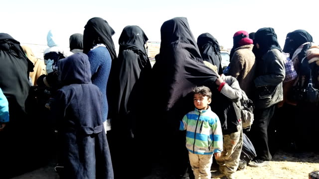 civilians who have fled fighting in bagouz wait to board trucks after being screened by members of the syrian democratic forces at a makeshift... - syria stock videos & royalty-free footage