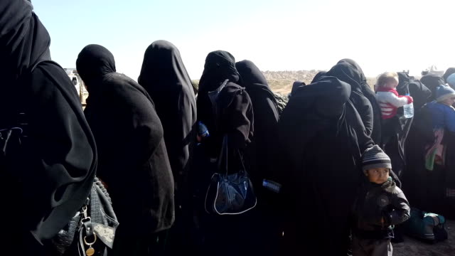 civilians who have fled fighting in bagouz wait to board trucks after being screened by members of the syrian democratic forces at a makeshift... - isis stock videos and b-roll footage