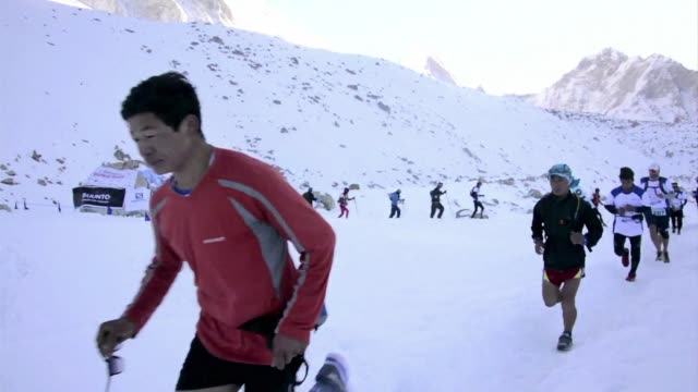 vídeos de stock e filmes b-roll de clad in trekking boots and snow goggles more than 150 runners take part in the world's highest marathon in the foothills of mount everest passing... - roupa de esqui