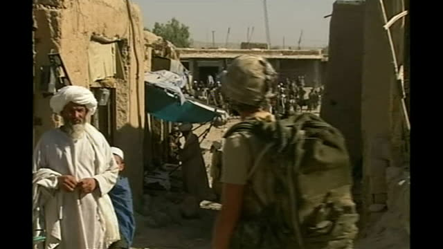 claims of civilians deaths following nato air strike; tx 5.10.2007 british troops behind bunker wall and on patrol through market area soldier... - civilian stock videos & royalty-free footage