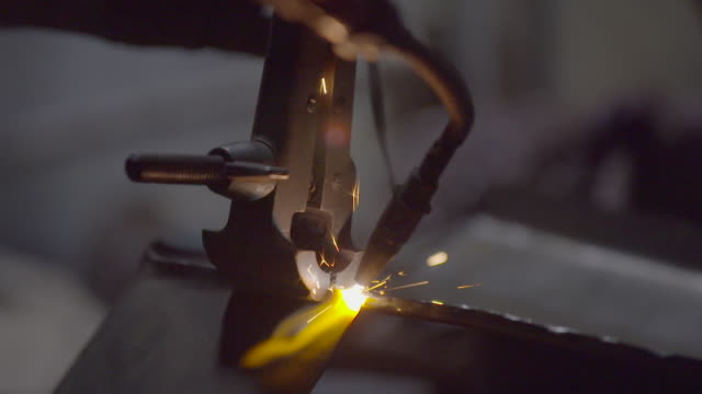 clamp holds sheet metal as flames and sparks weld seam - clamp stock videos & royalty-free footage