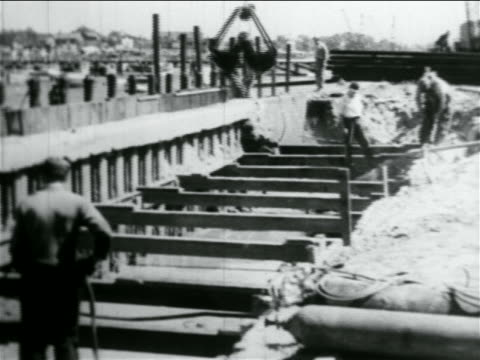 clamshell bucket dropping dirt + men working in wpa construction project / documentary - 1934 stock videos & royalty-free footage