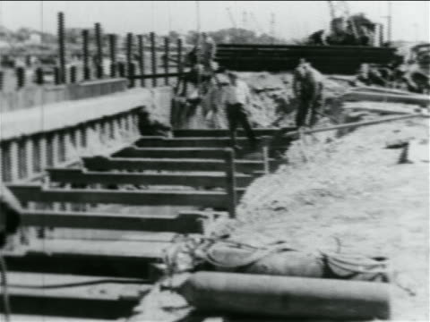 b/w 1934 clamshell bucket lifting mud men working in wpa construction project / documentary - new deal video stock e b–roll