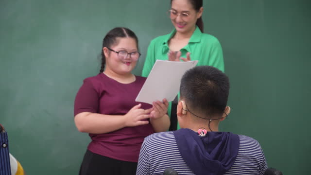 clap your hands to a girl with down syndrome talking, communicating, practicing presentation with positive emotion of smiling to friends in a wheelchair an asian teacher. student boy in a wheelchair and beautiful woman clapping to her smiling in school. - speech stock videos & royalty-free footage