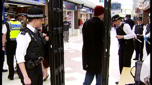 clapham: int back view train passengers through knife arch metal detector, police searching pockets and using hand held metal detector scanner to... - セキュリティスキャナ点の映像素材/bロール