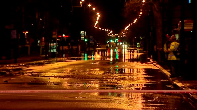 clapham road remains closed following water pipe burst; england: london: ext / night flooded road with water pouring into street cordon tape across... - road closed englisches verkehrsschild stock-videos und b-roll-filmmaterial