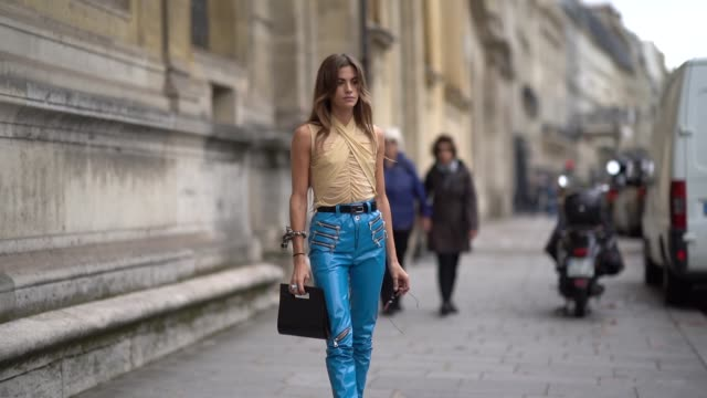 clara berry wears a light yellow gathered and draped top a black belt shiny blue vinyl pants with zips a small black crocodile pattern shopping bag... - platform shoe stock videos and b-roll footage