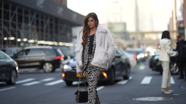 vídeos de stock e filmes b-roll de clara berry wears a white fluffy jacket, a black top, a black and white jacket and flared pants with printed hearts, sneakers, white socks, outside... - ténis calçado desportivo