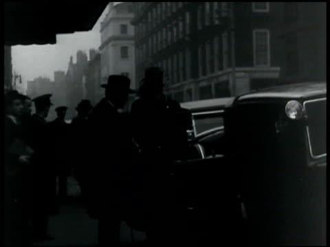 vídeos de stock, filmes e b-roll de claridges sign. british attendees of london naval conference: sir john simon ramsey mcdonald getting into cab. - 1935
