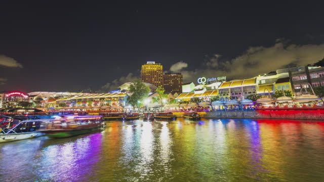 t/l clarke quay at night with boat taxis on the river - 水上タクシー点の映像素材/bロール