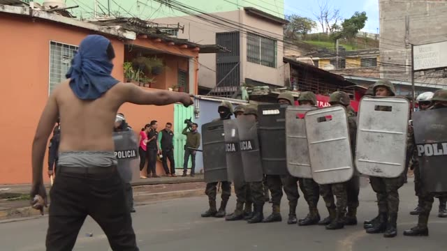 Clashes between protesters armed with rocks and police armed with tear gas erupt in Tegucigalpa on Wednesday the day after Honduran President Juan...