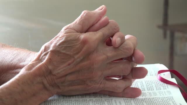 clasped hands of a senior woman praying over the bible - 神 個影片檔及 b 捲影像