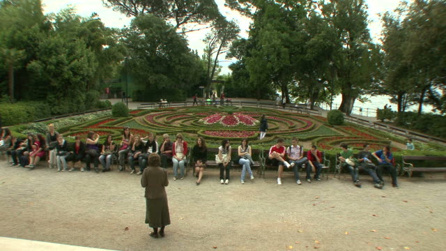 ws class being held in city park / opatija, croatia  - legs crossed at knee stock videos & royalty-free footage