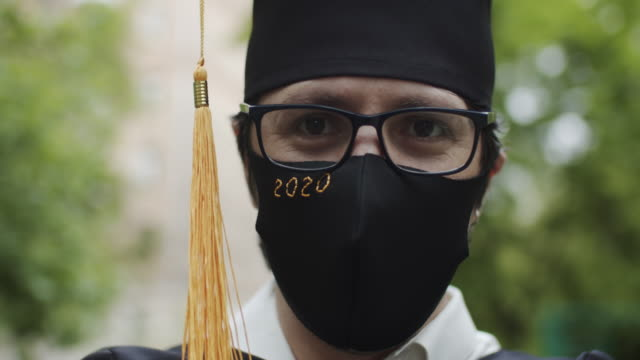klasse von 2020 absolvent trägt schutzmaske und graduierung kleid und maske - besonderes lebensereignis stock-videos und b-roll-filmmaterial