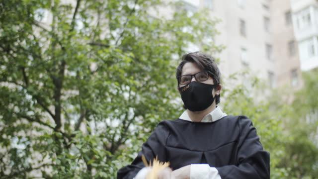 klasse von 2020 absolvent trägt schutzmaske und graduierung kleid und maske - abstand halten infektionsvermeidung stock-videos und b-roll-filmmaterial