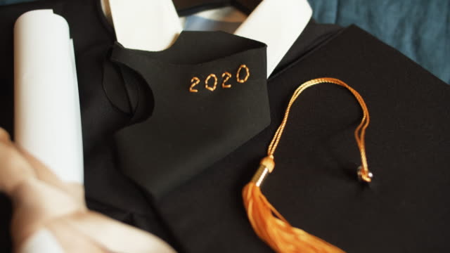 class of 2020 graduation gown and cap with protective mask due to covid-19 pandemic - memorial event stock videos & royalty-free footage