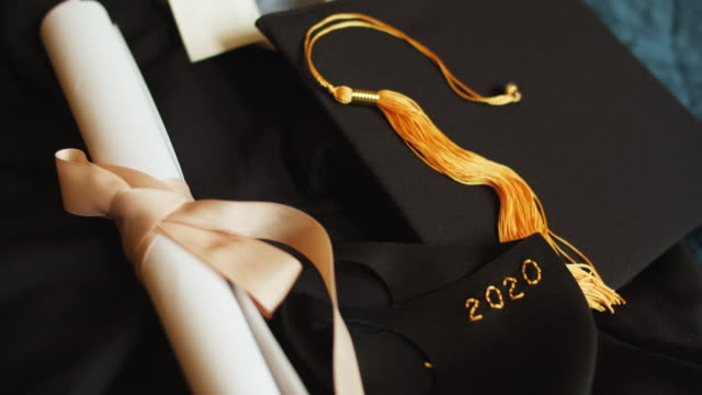 class of 2020 graduation gown and cap with protective mask due to covid-19 pandemic - cap stock videos & royalty-free footage