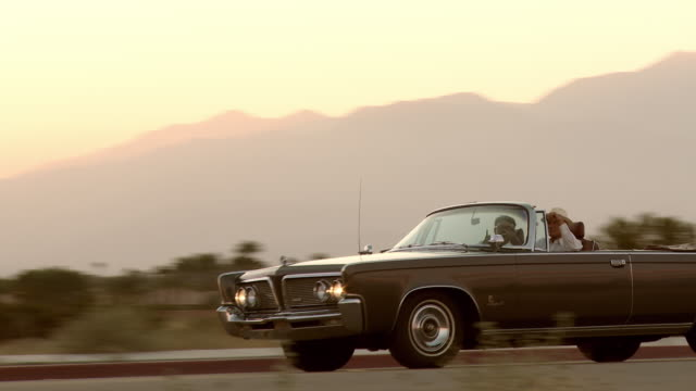 ls pan classic 1960s american convertible driving on desert road - collector's car stock videos and b-roll footage