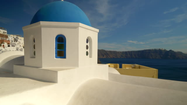 classic blue domed church in oia village on the mediterranean island of santorini - insel santorin stock-videos und b-roll-filmmaterial