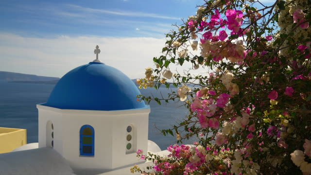 vídeos de stock, filmes e b-roll de classic blue domed church in oia village on the mediterranean island of santorini - oia santorini