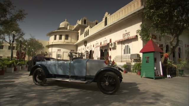 a classic blue rolls royce parked outside a palace in udaipur, india. - rolls royce stock videos and b-roll footage