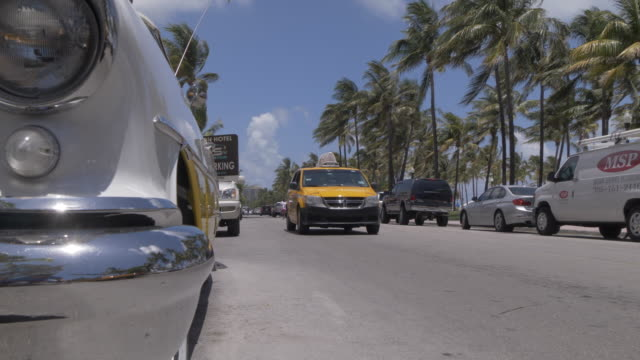 vidéos et rushes de classic car and yellow cab passing on ocean drive, south beach, miami, florida, united states of america, north america - miami