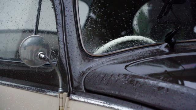 古典的な車は、雨の滴で覆われています。2 つのトーン古いレトロな車が自宅の駐車場に。 - フロントガラス点の映像素材/bロール