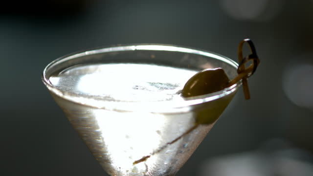a classic, cold refreshing martini cocktail with olive is placed on a table. - after work stock-videos und b-roll-filmmaterial