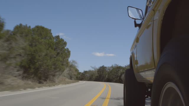 vidéos et rushes de classic ford bronco speeds around curve on rural two lane highway - aller tranquillement