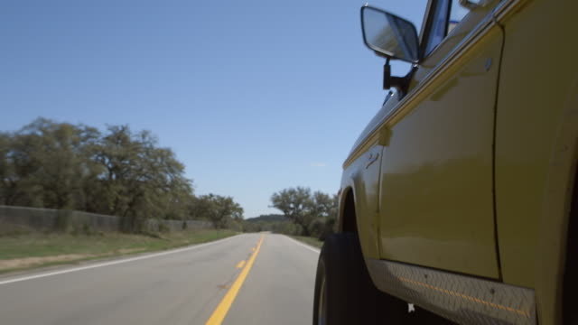 vidéos et rushes de classic ford bronco speeds down two lane highway - aller tranquillement