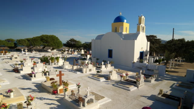 vídeos de stock, filmes e b-roll de classic greek orthodox blue domed church and cemetery on the mediterranean island of santorini, greece - oia santorini