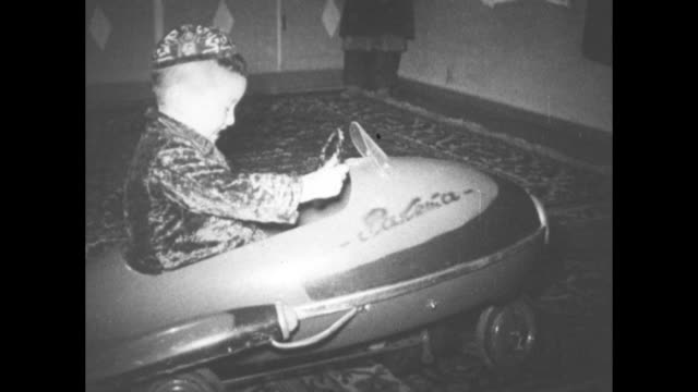 Classic image of little boy in space ship pedal car this may be in a foreign country not the USA