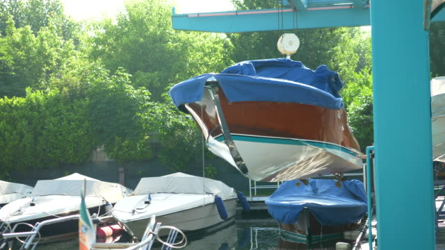 a classic luxury wooden runabout boat gets put in a marina with a crane. - 唯一点の映像素材/bロール