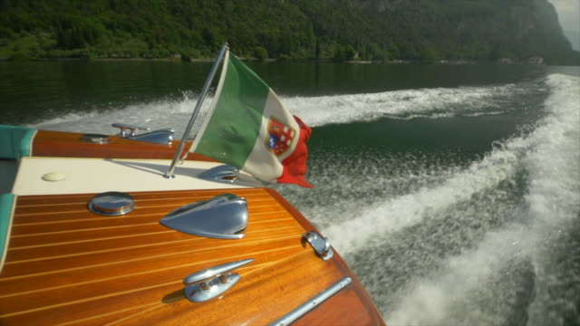 a classic luxury wooden runabout boat with an italian flag on a lake. - slow motion - exklusiv stock-videos und b-roll-filmmaterial