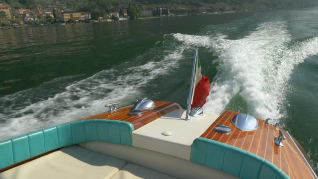 A classic luxury wooden runabout boat with an Italian flag on a lake. - Slow Motion
