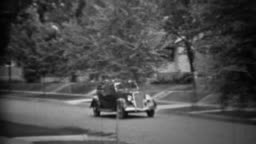 1935: Classic new black Plymouth car driving residential neighborhood.