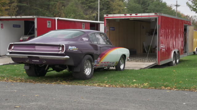 A classic Plymouth Barracuda stands in front of a red trailer at Lebanon Valley Dragway New York State USA FKAX911W Clip taken from programme rushes...