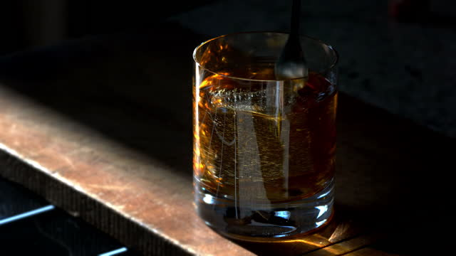 classic prohibition manhattan cocktail in old fashioned rocks glass being stirred - scotch whiskey stock videos & royalty-free footage