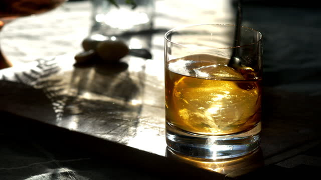classic prohibition manhattan cocktail in old fashioned rocks glass, with sphere ice cube, being stirred. - scotch whiskey stock videos & royalty-free footage