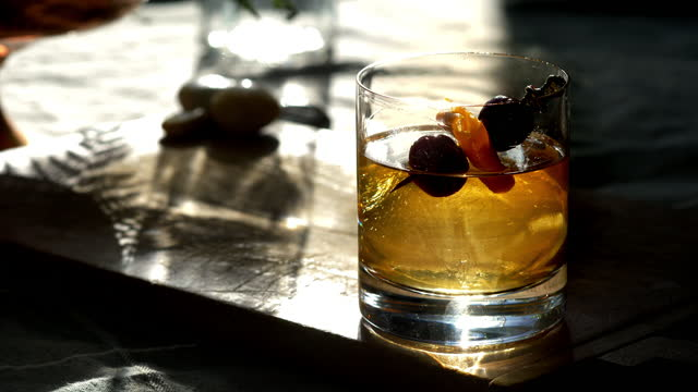 classic prohibition manhattan cocktail in old fashioned rocks glass, with sphere ice cube. - scotch whiskey stock videos & royalty-free footage