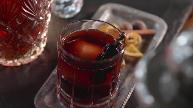 classic prohibition manhattan old fashioned cocktail in cut crystal rocks glass being garnished with cherries - 穀物 ライムギ点の映像素材/bロール