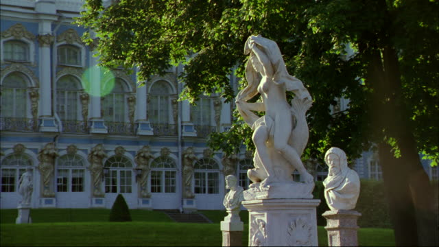 Classic statues stand on a Peterhof lawn.