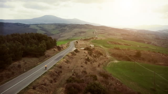 classic tuscan view from a drone: cyclist on the road - tuscany stock videos & royalty-free footage